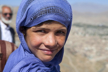 AFG0012AW A girl dressed in a headscarf smiles while standing on a hillside, Kabul Afghanistan