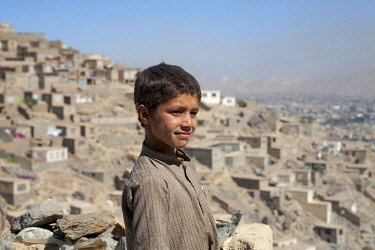 AFG0013AW A boy stands on a hillside covered with stone houses, Kabul, Afghanistan