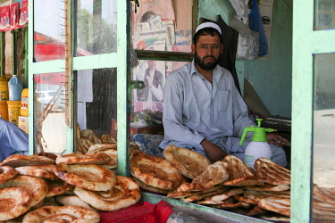 AFG0020AW A baker sits in his shop selling flat bread, Kabul, Afghanistan