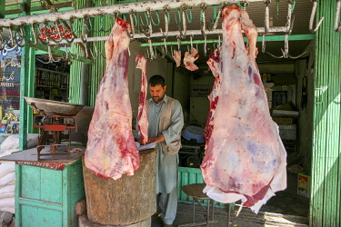 AFG0022AW A butcher stands in his shop with meat hanging on hooks around him, Kabul, Afghanistan
