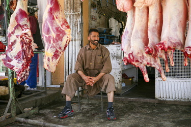 AFG0023AW A man sits in his butcher�s shop, surrounded by hanging meat, in Kabul, Afghanistan