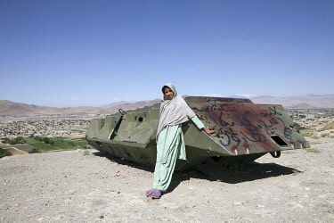 AFG0024AW A girl leans on an old military tank on a hill in Kabul, Afghanistan