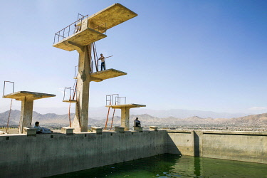 AFG0027AW Boys play on the diving board at an outdoor swimming pool in Kabul, Afghanistan. This Soviet-built Olympic-sized pool was used as an execution ground by the Taliban.