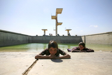 AFG0028AW Two children lie on the concrete at the edge of an outdoor swimming pool in Kabul, Afghanistan. This Soviet-built Olympic-size pool was used as an execution ground by the Taliban.