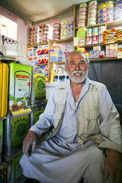 AFG0029AW An elderly man sits in his grocery shop in Kabul, Afghanistan