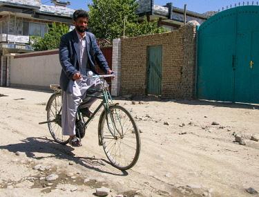 AFG0030AW Man riding a bike down a street, Kabul, Afghanistan