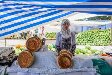 TAJ1138AW A Muslim woman selling bread at a stall on Dushanbe Market, Tajikstan