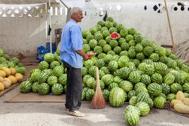 TAJ1142AW A man standing outside a watermelon stall, Dushanbe Market, Dushanbe, Tajikistan