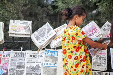 TAJ1144AW Girl reading a newspaper at a newspaper stand, Dushanbe, Tajikistan