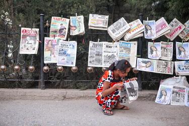 TAJ1145AW Girl reading a newspaper at a newspaper stand, Dushanbe, Tajikistan