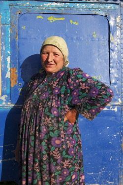 TAJ1149AW Tajik woman stands outside her home on the Pamir Highway, Tajikistan
