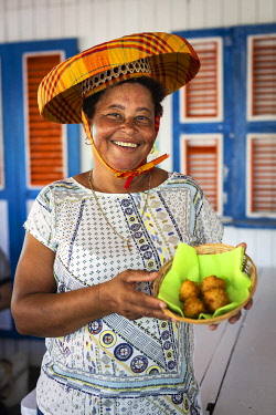 FRA11945AW Guadeloupe, Iles des Saintes, The owner of a snack bar in Terre de Haut island shows typical accras croquettes.