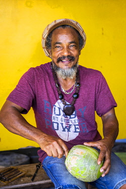 FRA11946AW French West Indies, Guadalupe, Bouillante, A shop owner carves a Guadalupe pumpkin.