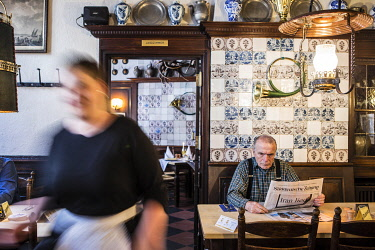 GER12240AW A man reads a newspaper at a table in the Altes Gasthaus Leve, Munster, Germany