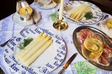 GER12242AW A table set for two with spargel, air-dried ham, boiled potatoes, hollandaise sauce and a glass of white wine, Altes Gasthaus Leve, Munster, Germany
