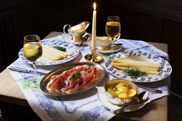 A table set for two with spargel, air-dried ham, boiled potatoes and a glass of white wine, Altes Gasthaus Leve, Munster, Germany