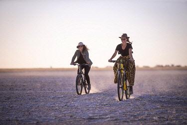BOT5719AW Women riding bicycles, Makgadikgadi Salt Pans, Botswana
