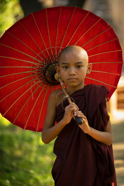 MYA2822AW Portrait of novice monk with red umbrella, Bagan, Mandalay Region, Myanmar