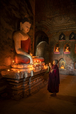 A novice monk holding a burning candle while praying by Buddha statue, UNESCO, Bagan, Mandalay Region, Myanmar