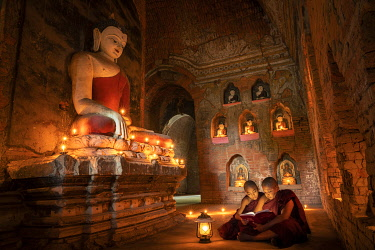 Two novice monks studying inside a temple under big Buddha statue, UNESCO, Bagan, Mandalay Region, Myanmar