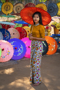 MYA2876AW Portrait of young woman with colorful umbrella against display at street market, Mandalay, Mandalay Region, Myanmar