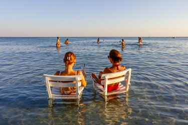 AS37AKA2160 Two women sitting on armchairs in the water, beach in Cesme, Izmir, Turkey.