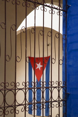 CA11JME0236 Cuba, Vinales, Cuban flag in courtyard and wrought iron gate.
