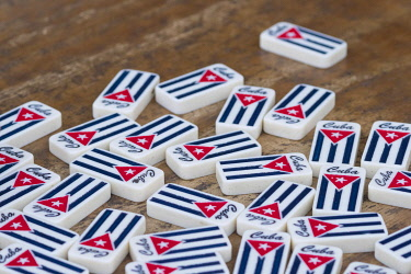 CA11JME0230 Cuba, Havana, pile of dominoes with Cuban flag on wood table.