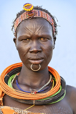 SUD1295 Africa; South Sudan; Kapoeta. A portrait of a Toposa lady in traditional attire and scarification on her forehead and chest.