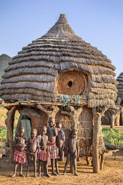 Africa; South Sudan; Kapoeta. Toposa children stand beside their family's granary. In a year of good rainfall, a supplementary granary is placed beneath the main granary.