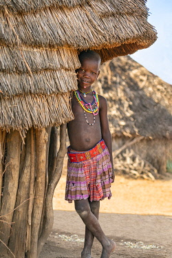 SUD1321 Africa; South Sudan; Kapoeta. A young Toposa girl in traditional attire stands at the entrance to her thatched house.