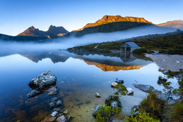 Reflections of Cradle Mountain and boat shed in Dove Lake with mist hanging over the water. Cradle Mountain National Park, Davenport and Cradle Mountain, Tasmania, Australia