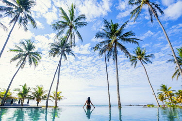 Southeast Asia, Indonesia, Bali, Candidasa. A woman looking out over the ocean from an infinity pool. Back turned to camera MR