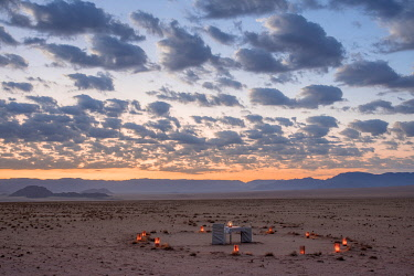 Namibia, NamibRand Nature Reserve, Kwessi Dunes, a dining table for two in the desert at sunset.