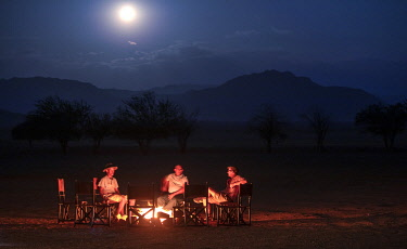 NAM6778 Namibia, NamibRand Nature Reserve, Kwessi Dunes, guests and guide sit aroiund the fire place at night.