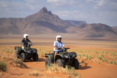 NAM6805 Namibia, NamibRand Nature Reserve, Kwessi Dunes, a guide and his guest explore the desert on quad bikes.
