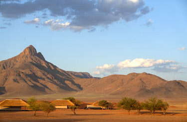 Namibia, NamibRand Nature Reserve, Kwessi Dunes, guests chalets with sand dunes and mountains behind.