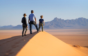 NAM6811 Namibia, NamibRand Nature Reserve, Kwessi Dunes, a guide and guests enjoy the views from the top of a sand dune.