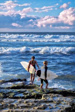 US12LEN0121 Young surfers entering surf, Maui, Hawaii, USA.