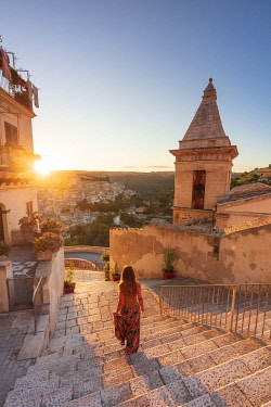 ITA15910AW Ragusa Ibla, Sicily. A woman walking on the stairs with Ragusa old town in the background at sunrise