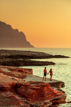ITA15963AW San Vito lo Capo, Sicily. A couple enjoying the sunset on the rock formations along the coastline called Macari at sunset