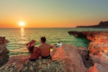 ITA15965AW San Vito lo Capo, Sicily. A couple enjoying the sunset on the rock formations along the coastline called Macari at sunset