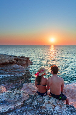 ITA15966AW San Vito lo Capo, Sicily. A couple enjoying the sunset on the rock formations along the coastline called Macari at sunset