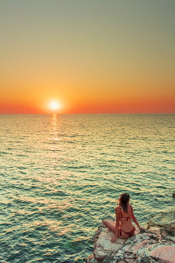 ITA15968AW San Vito lo Capo, Sicily. A person enjoying the view of the sun setting along the rock formations of the coastline called Macari near San Vito Lo Capo