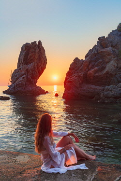 ITA15983AW Cefalu, Sicily. A woman enjoying the rocky coastline and sea at Kalura beach at sunrise near Cefalu