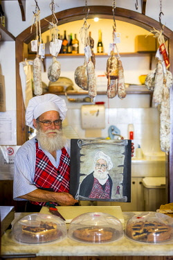 ITA16057AW Italy, Serchio Valley. Shop owner showing a portrait of himself.