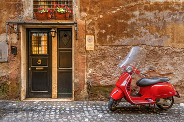 ITA16132AW Parked red Vespa scooter in a cobbled street of Rome, Lazio, Italy
