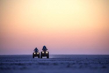 BOT5826 Camp Kalahari, Makgadikgadi, Botswana, a family and their guide whizz across the salt pans on quad bikes.