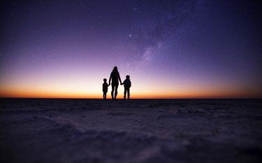 BOT5876 Camp Kalahari, Makgadikgadi, Botswana, a woman and two children look at the night sky from the salt pans.