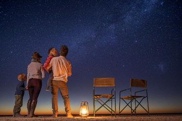 BOT5877 Camp Kalahari, Makgadikgadi, Botswana, a family look at the night sky from the salt pans.